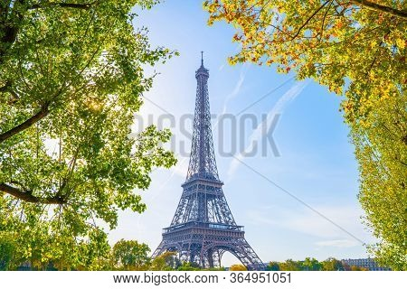 Eiffel Tower In Paris Landscape With Blue Sky. Eiffel Tower Framed With Colorful Trees. The Most Fam