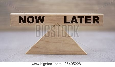 The Concept Of The Balance Of Words Between Now And Later On Wooden Scales On A Light Background. Bu