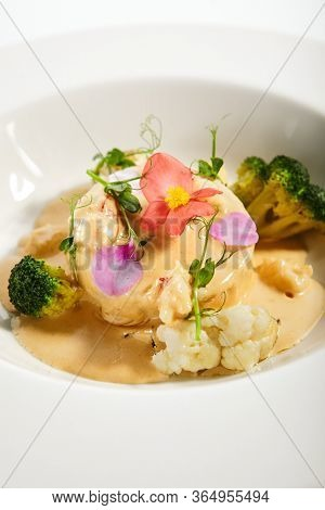 Pike fish souffle in plate. Served luxury cuisine. Norway lobster with bisque sauce and langoustines on white. Seafood restaurant high menu food portion. Delicious supper, main course