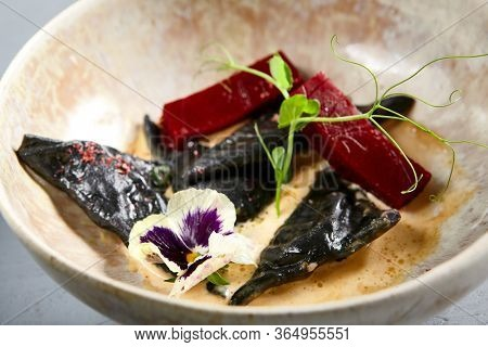 Mussels in black in beige bowl. Ravioli with lingonberry confit and creamy sauce close up. Gourmet appetizer with peas twigs and violet flowers decoration. Served delicatessen, seafood