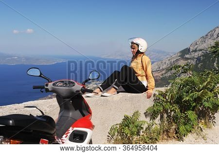 The Girl On The  Scooter Stopped In The Mountains Of Croatia. A Beautiful Summer Landscape From The