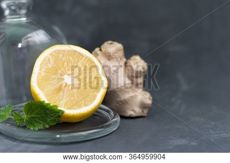 Fresh Ginger Root With Lemon And Mint Or Mellis Leaves Under A Transparent Glass Bell On A Gray Hete