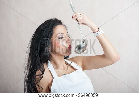 Girl Blowing In The Kitchen Scoop. Portrait Of A Girl With A Scoop