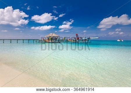Ari Atoll, Maldives - 05.12.2019: Maldives Seaplane On Luxury Resort, Wooden Jetty Loading The Plane