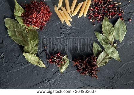 Raw Pasta Rests On A Table With Pepper Bay Leaf Badyan And Spicy Spices On A Dark Background