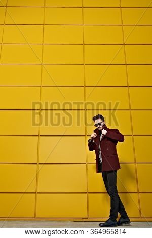 Urban style. Fashion portrait of a stylish young man in a coat and sunglasses posing on a street by the yellow industrial wall. Male fashion. Copy space.