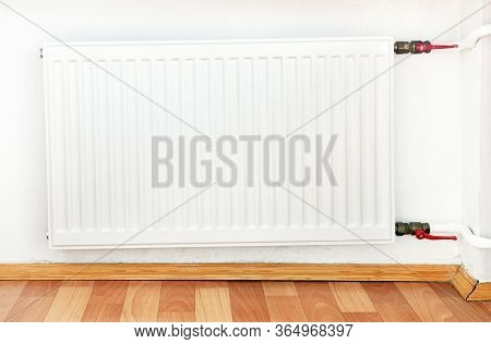 White Radiator In An Apartment. Radiator.white Radiator With Tap To Shut Off The Water Supply To The