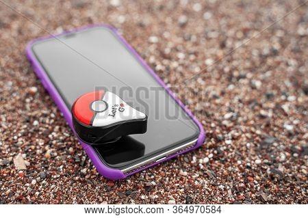 Budva, Montenegro March 07, 2020: Smartphone In Lilac Case Lies On Fine Gravel. Accessory Is Pokemon