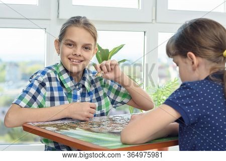 Children Assemble A Puzzle From Puzzles, One Of Them Looked Into The Frame