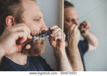 Selfcare During Quarantine Isolation. Adult Handsome Caucasian Man Cutting Moustache And Beard Himse