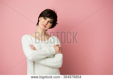 Beautiful young female model posing at studio over pink background looking at camera. Pretty brunette woman portrait. Girl thinks, dreams, makes plans for the future