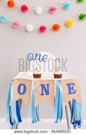 Festive Background Decoration For Birthday Celebration. Letters Text One And One Candle In Small Cup