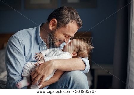 Middle Age Caucasian Father Kissing Sleeping Newborn Baby Girl. Parent Holding Rocking Child Daughte