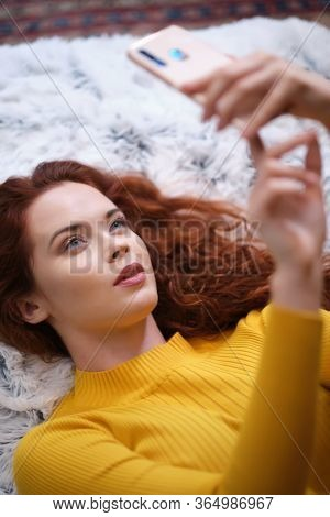 Young happy woman using mobile phone for video call , gesturing hi to friends, relatives . Beautiful young woman using mobile phone lying on the bed