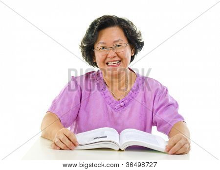 Asian senior woman reading book over white background