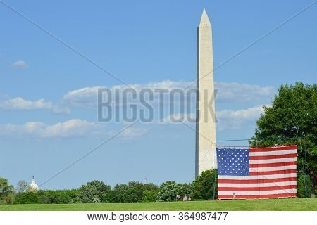 Washington Monument and a large National flag erected in the Constitution Gardens Park during Memorial weekend  - Washington DC United States of America