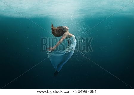 Elegant Girl Dancer In White Dress In A State Of Levitation Under The Deep Waters Of The Ocean With
