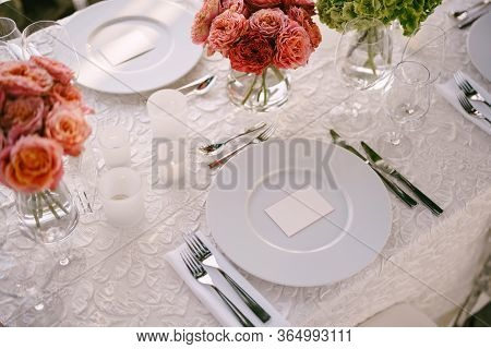 Wedding Dinner Table Reception. View From Above On White Round Plates Close-up. Bouquets Of Pink, Or
