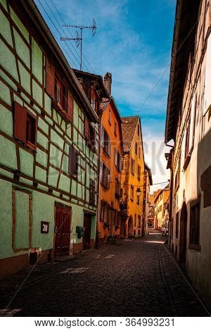 colorful halftimbered houses along a narrow street with cobblestones in the medieval town of Riquewihr, Alsace Region, France