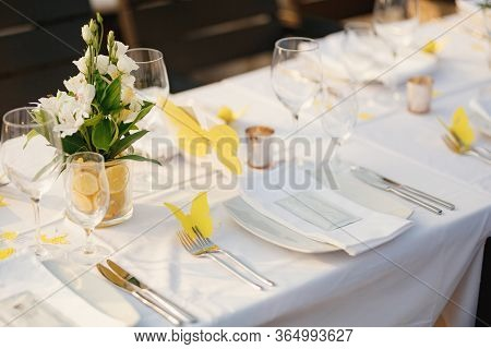 Wedding Dinner Table Reception. Glass Transparent Bath With Sliced Lemons And A Bouquet Of White Als