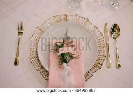 Wedding Dinner Table Reception. Gold Plate Under White, Pink Fabric Towel, Pink Flower With Silk Rib