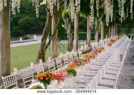 Wedding Dinner Table Reception. A Very Long Table For Guests With A White Tablecloth, Floral Arrange
