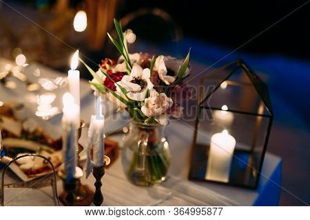 Wedding Dinner Table Reception. A Bouquet Of Flowers In A Glass Vase On The Table At Night. White Ca