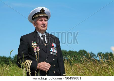 Grandfather in form, cap, ordens, medals stand near forest