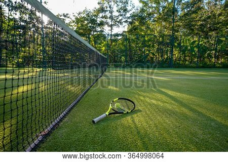 Tennis Ball And Racket In The Artificial Grass Tennis Court.