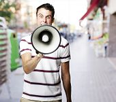 portrait of young man shouting with megaphone at street poster