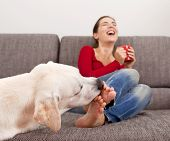 Woman drinking coffee on the sofa with her dog licking her toes poster