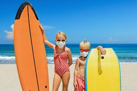 Funny Kids With Surf Boards Wear Protective Mask On Sea Beach. Cancelled Cruises, Tours Due Coronavi