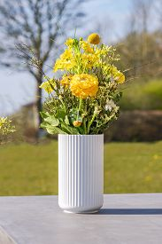 White Vase With Yellow Wildflowers On A Table On A Countryside Terrace