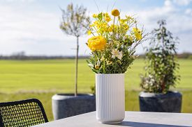 Yellow Wildflowers In A White Vase On A Terrace In A Rural Environment