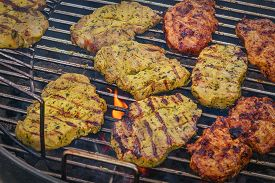 Grilled Pork Chops With Spices On A Hot Grill With Flames And Barbeque Flavor