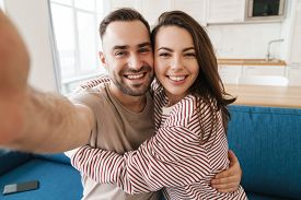 Photo closeup of young joyful couple hugging and smiling while taking selfie photo in kitchen