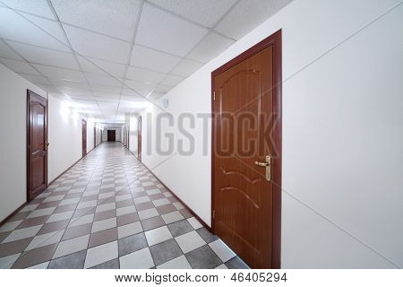 Long bright hallway with wooden doors and floor covered with tiles.