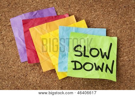 slow down - lifestyle concept or advice - handwriting on colorful sticky notes