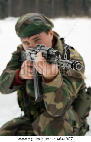 A Young Man In A Camouflage Shoots From The Automat Of Kalashnikova
