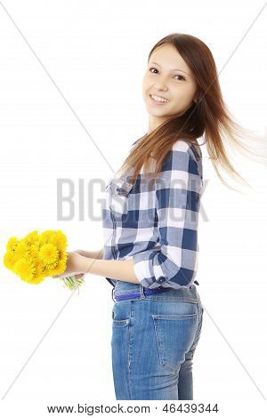 Girl With Bouquet Yellow Wildflowers. Teenage Girl In Jeans And A Plaid Shirt, Holding A Bouquet Of