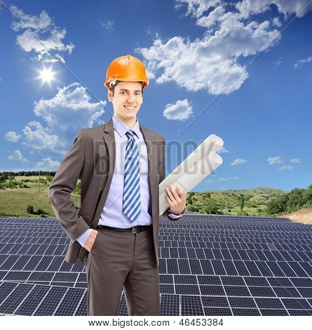 Architect wearing helmet and holding blueprints, with solar photovoltaic cell panels in the background, shot with a tilt and shift lens