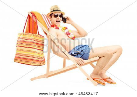 Man enjoying on a sun lounger while talking on a mobile phone, isolated on white background