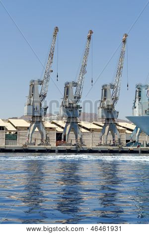 Row of cranes and their reflections in the sea in Eilat harbor Israel