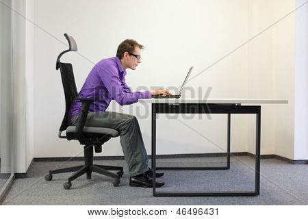 bad sitting posture at laptop .short-sighted business  man  on chair in his office