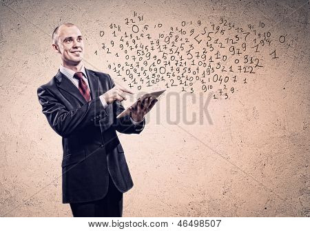 Young businessman holding tablet pc thinking over idea