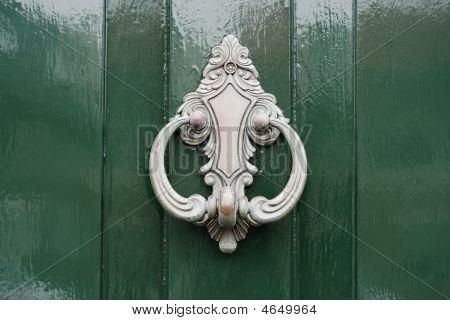 Doorknocker In Silver On Green Painted Wooden Door