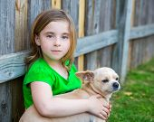 Blond happy girl with her chihuahua doggy portrait on backyard fence poster