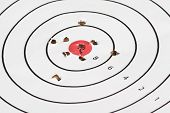 Close up of a shooting target with bullet holes in and around the red bullseye in the center poster