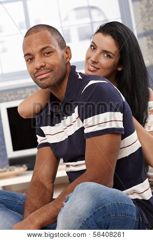 Attractive young interracial couple sitting, embracing at home, smiling.