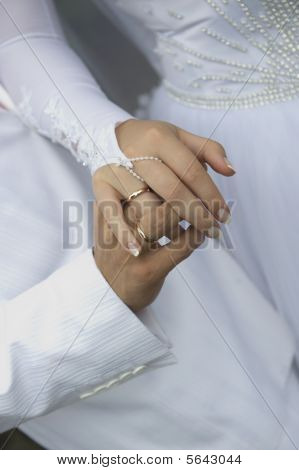hands of newly-weds with the interlaced fingers in white poster